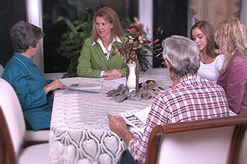 Family members sitting at a table discussing Preplanning