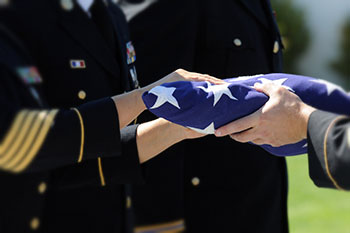 Close up of hands passing a folded flag to another set of hands